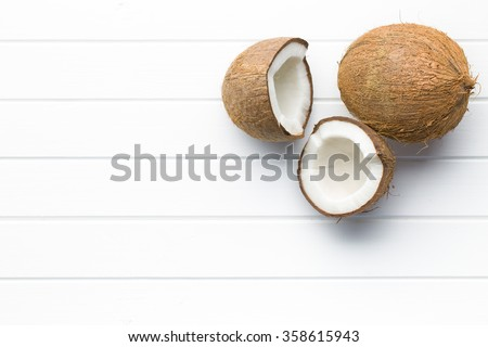 halved and whole coconut on white table