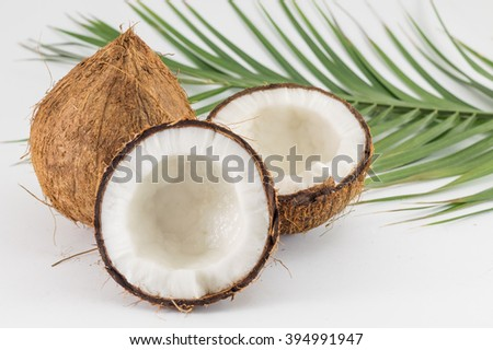 Halved and whole fresh coconuts with coconut leaves on white