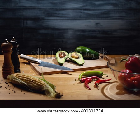 Halved and whole ripe avocados on wooden board with knife. Low key shot, light on board, some vegetables around on table. Copy space.