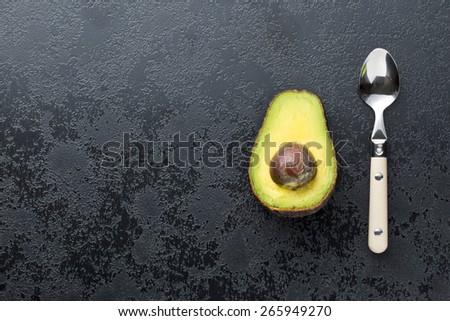 halved avocado on old black table - stock photo
