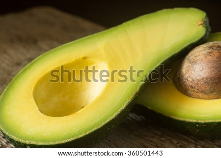 Halved avocado on old wooden board. Close up image