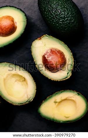 Halved avocados over black background. Top view. Avocado spread. Avocado pasta. Guacamole  - stock photo