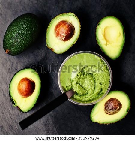 Halved avocados over black background. Top view. spread.  pasta. Guacamole  - stock photo