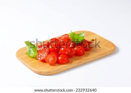 halved cherry tomatoes decorated with fresh basil, on the wooden cutting board - stock photo