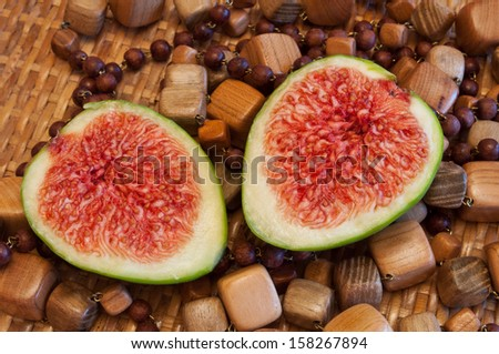 Halved fig on wooden beads background - stock photo