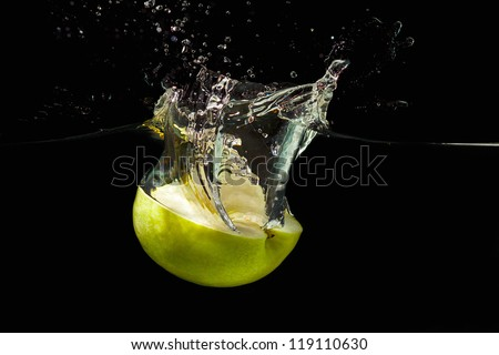 Halved ripe green apple falling into the water with a splash on black background - stock photo