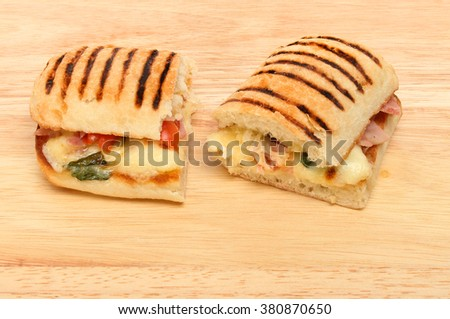 Halves of a mozzarella, ham, tomato and basil panini on a wooden chopping board