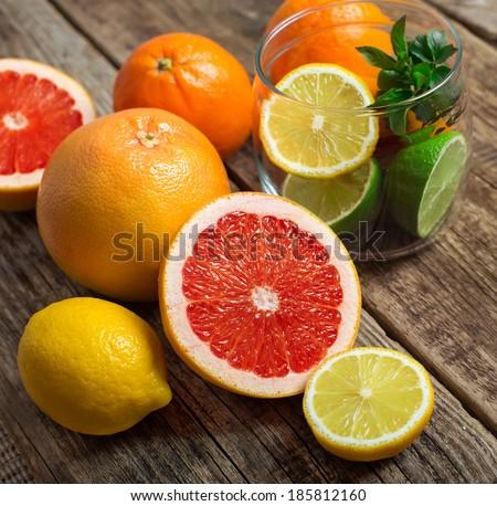 Halves of citrus fruits on wooden background. Orange, grapefruit, lime, lemon, tangerine cut rings. - stock photo