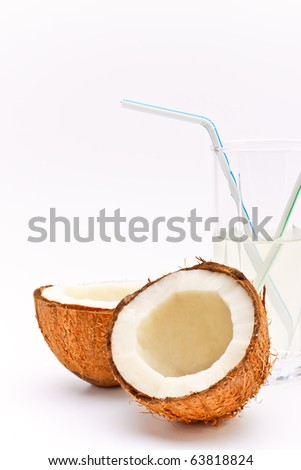 halves of coconut and glass with coco milk - stock photo