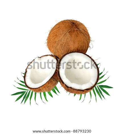halves of coconut on green leaves isolated on white
