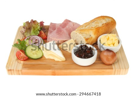 Ham and cheese ploughman's lunch on a wooden serving platter isolated against white - stock photo