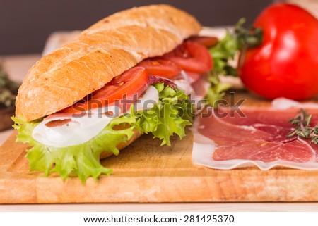 Ham and cheese salad submarine sandwich from fresh baguette on wooden background - stock photo