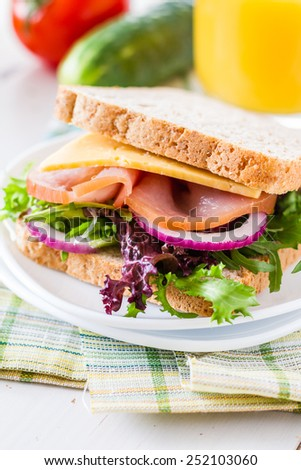Ham and cheese sandwich on white plate, juice, white wood background, closeup