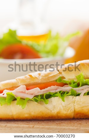 Ham and cheese sandwich with lettuce and tomato.