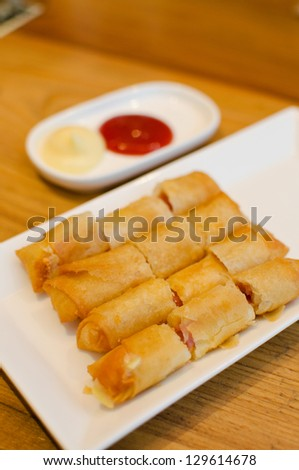 Ham and cheese spring rolls with sauce - stock photo