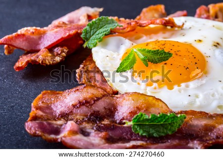 Ham and Egg. Bacon and Egg. Salted egg and sprinkled with black pepper and green herb decoration. English breakfast.  - stock photo
