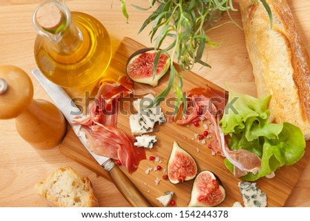 Ham, cheese and figs on the wooden board - stock photo