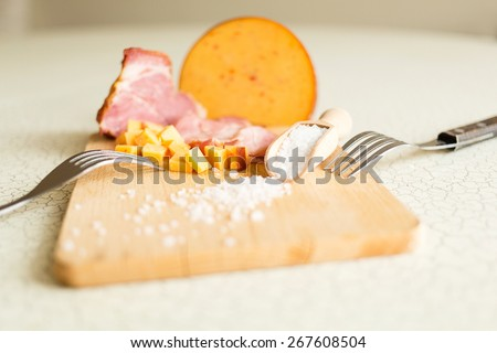 Ham, cheese, bread and salt on a wooden cutting board. The breakfast in the village. Snack with beer or nosh. - stock photo