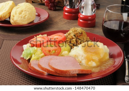 Ham dinner with cornbread stuffing, mashed potatoes and gravy - stock photo