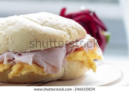 Ham & eggs sandwich on wooden board - stock photo