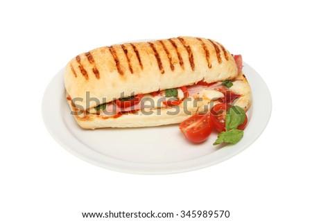 Ham, mozzarella, tomato and basil pannini on a plate isolated against white - stock photo