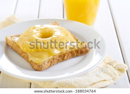 Ham, pineapple and cheese toast and glass of orange juice