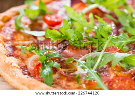 Ham Pizza with rocket, fresh tomatoes, garlic and cheese - stock photo
