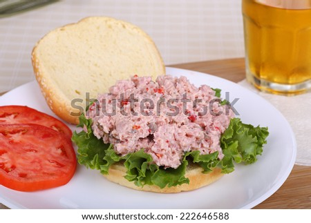 Ham salad and lettuce on a bun with sliced tomatoes on the side - stock photo