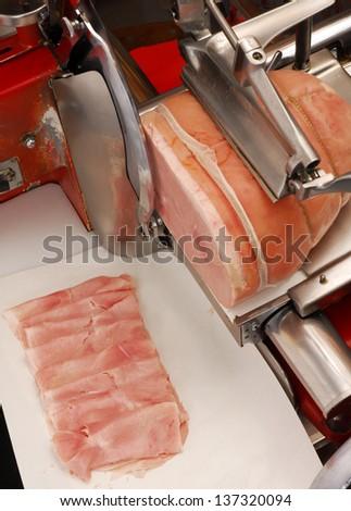 Ham slicer and prosciutto ham in a warehouse. - stock photo