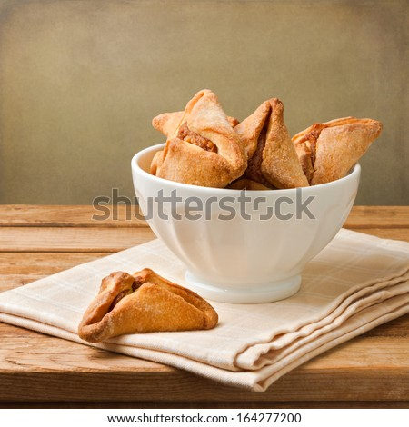 Hamantaschen cookies for Jewish festival of Purim on wooden table - stock photo