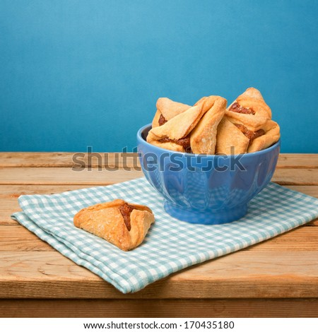 Hamantaschen cookies for Jewish festival of Purim on wooden table over blue background - stock photo