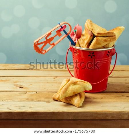 Hamantaschen cookies in bucket with grogger noise maker - stock photo