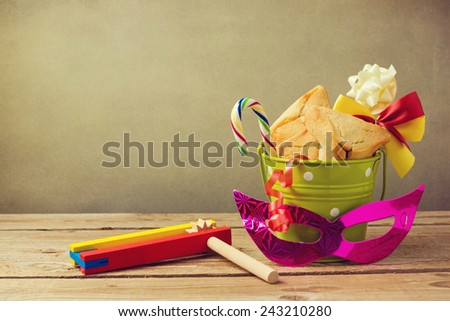 Hamantaschen cookies in bucket with grogger noise maker and carnival mask. Gift for purim festival - stock photo