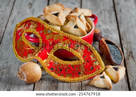 Hamantaschen cookies or Haman's ears and carnival masks for Purim celebration (jewish holiday). - stock photo