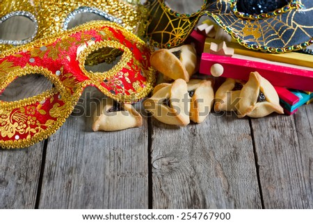 Hamantaschen cookies or Haman's ears, noisemaker and carnival masks for Purim celebration (jewish holiday). Copy space background. - stock photo