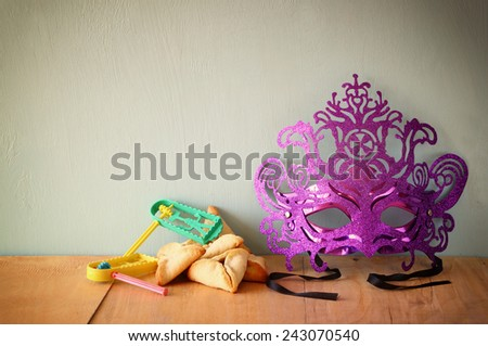 Hamantaschen cookies or hamans ears and mask for Purim celebration (jewish holiday)  - stock photo