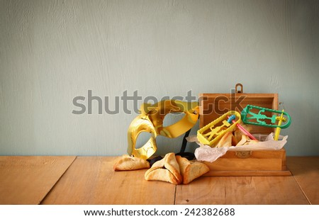 Hamantaschen cookies or hamans ears and mask for Purim celebration (jewish holiday). filtered image  - stock photo