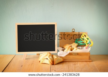 Hamantaschen cookies or hamans ears and noisemaker  for Purim celebration (jewish holiday) - stock photo