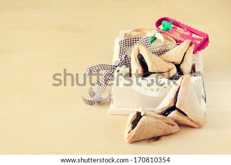 Hamantaschen cookies or hamans ears for Purim celebration in wooden box. vintage effect.  - stock photo
