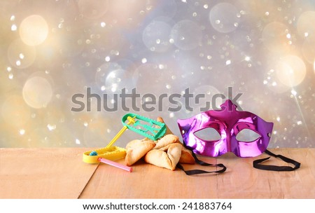 Hamantaschen cookies or hamans ears,noisemaker and mask for Purim celebration (jewish holiday) and glitter background  - stock photo