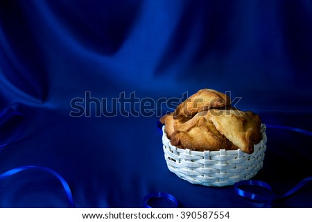 Hamantaschen or Haman's ears - triangular cookies for Jewish holiday of Purim on dark blue silk background - stock photo
