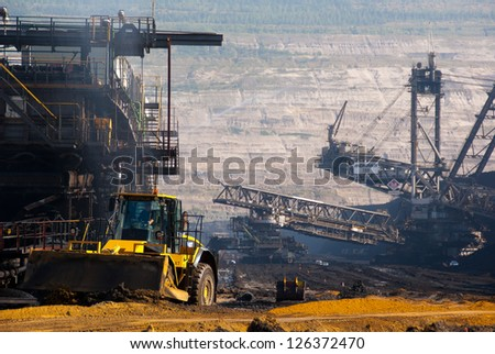 HAMBACH, GERMANY - SEPTEMBER 1, 2010: A shovel and one of the world's largest excavators digging lignite (brown-coal) in one of the deepest open-pit mines in Hambach, Germany on September 1, 2010 - stock photo