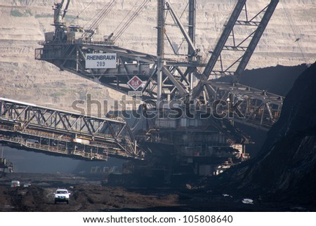 HAMBACH, GERMANY - SEPTEMBER 1: A 4-wheel drive and one of the world's largest excavators (background) digging lignite in of the world's deepest open-pit mines in Hambach on September 1, 2010. - stock photo