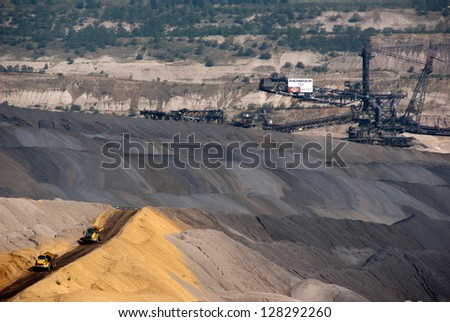 HAMBACH, GERMANY - SEPTEMBER 1: Very large trucks and one of the world's largest bucket-wheel excavators digging coal in one of the world's deepest open-pit mines in Hambach on September 1, 2010 - stock photo