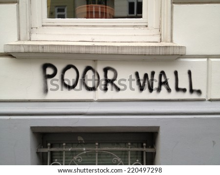 "HAMBURG, GERMANY - AUGUST 7, 2012: Building wall with ""POOR WALL"" written on it in black spray paint in Hamburg, Germany on August 7, 2012."