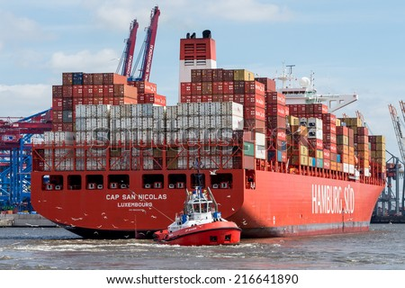 Hamburg, Germany - June 23, 2014: Small tug boat maneuvers large container ship