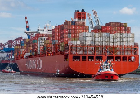 Hamburg, Germany - June 23, 2014: Tug boat pulls large container ship in the port of Hamburg