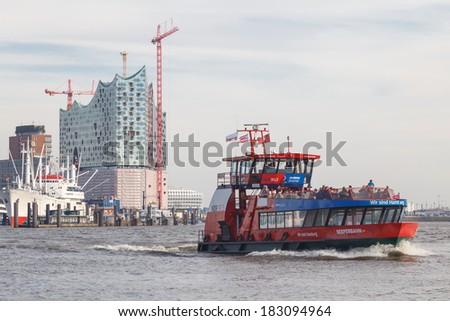 "HAMBURG, GERMANY - MARCH 20, 2014: Construction of the landmark Elbe Philharmonic building rises behind public harbor ferry ""Reeperbahn""  in Hamburg, Germany on March 20, 2014."