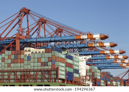 HAMBURG, GERMANY - MAY, 16. Container gantry cranes at the terminal Eurogate in the deepwater port Hamburg-Waltershof are loading/unloading containers of an vessel on May 16, 2014.
