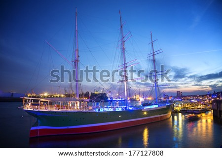 Hamburg, Germany. Night shot of the harbor during blue hour. Background the harbor, in front you see the Ricke Rickmers, an old sailing boat.  - stock photo